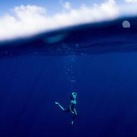 Woman underwater in the deep blue sea.