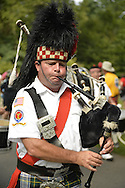 Old Westbury, New York, U.S. - August 23, 2014 - Clan Gordon Highlanders Pipe Band, of Locust Valley, are marching and playing bagpipe music at the 54th Annual Long Island Scottish Festival and Highland Games, co-hosted by L. I. Scottish Clan MacDuff, at Old Westbury Gardens, has bagpipes, booths, and family entertainment.
