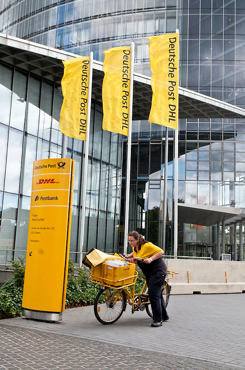Eine Postbotin schiebt ihr Fahrrad vor dem Hauptsitz der   - Deutsche Post DHL an |  Headquater Deutsche Post DHL AG
