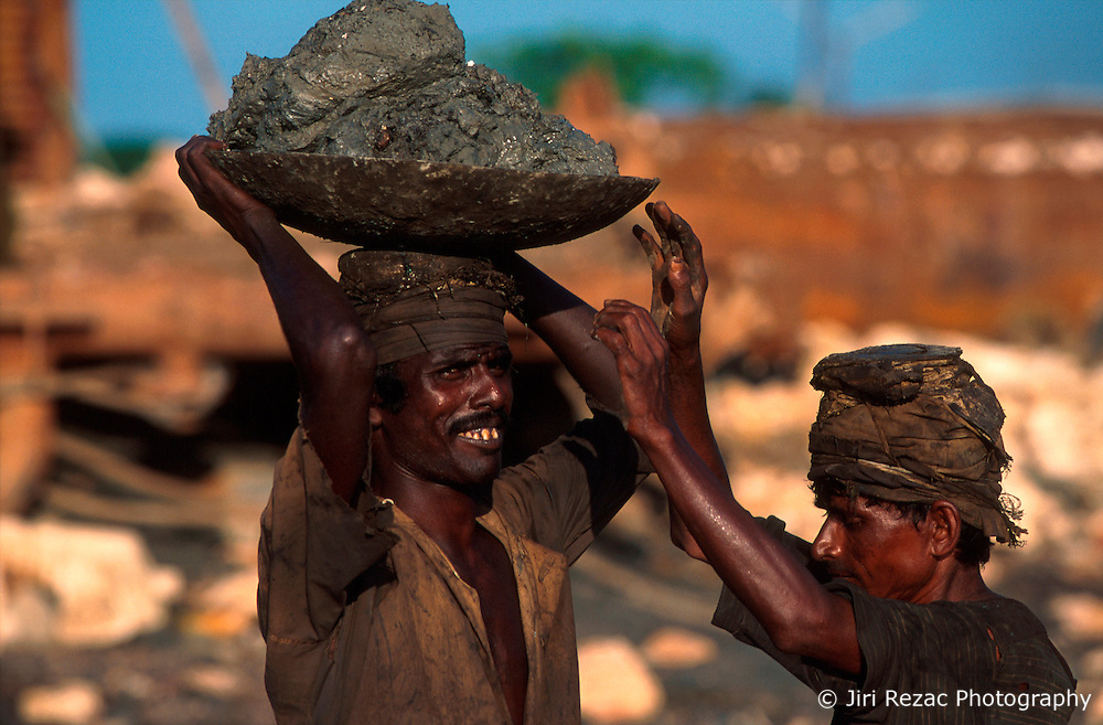 BANGLADESH CHITTAGONG MADHOM BIBIR HAT OCT00 - A labourer passes on a basket of mud to another in a human chain. Often the giant pieces of metal winched onto land contain large amounts of sticky mud which needs to me removed prior to dis-assembly...Several thousand labourers work on one medium-sized (50,000 ton) ship for a period of around three months, until it is completely dismantled and taken apart. ..Since Bangladesh does not possess mineral resources such as iron ore, it works out more cost-efficient to employ a large army of day-labourers to recycle the scrapped ships rather than to import ore. On average, a labourer can expect to earn a little more than 1 US Dollar per day...jre/Photo by Jiri Rezac..© Jiri Rezac 2000..Contact: +44 (0) 7050 110 417.Mobile: +44 (0) 7801 337 683.Office: +44 (0) 20 8968 9635..Email: jiri@jirirezac.com.Web: www.jirirezac.com..© All images Jiri Rezac 2000 - All rights reserved.