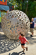 """Huntington, New York, U.S. 24th August 2013. A young boy has just stepped out from inside a rolling metal sculpture """"Sphere of Hope"""" which his father is still in, at the art event """"Off the Walls"""" Block Party, by SPARKBOOM, a Huntington Arts Council project created to help emerging artists, showcase talents, and help its artistic family network. The sculpture is by sculpture Steven Zaluski, and is created from human shapes welded together."""