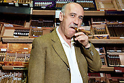 Portrait of mature tobacco shop owner smoking cigar in store
