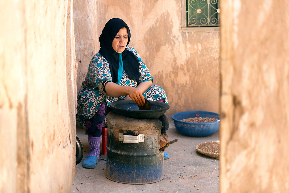 AOULOUZ, MOROCCO May 24th 2016 - Workers shell, toast and press argan nuts using a traditional grindstone to make traditional Moroccan argan oil at an argan farm in Agouni n Fad village near Aoulouz, Taliouine & Taroudant Province, Souss Massa Draa region of Southern Morocco.