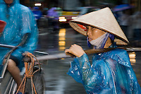 Street vendor walking the street's in the old quarter of Hanoi during a rain storm. Hanoi, estimated population 3,058,000(2004), is the capital of Vietnam. From 1010 until 1802, it was the political center of an independent Vietnam with a few brief interruptions. It was eclipsed by Hu during the Nguyen Dynasty as the capital of Vietnam, but served as the capital of French Indochina from 1887 to 1945. From 1945 to 1976, it was the capital of North Vietnam..The city is located on the right bank of the Red River. Hanoi is located 1760 km (1094 mi) north of Ho Chi Minh City (formerly Saigon). .