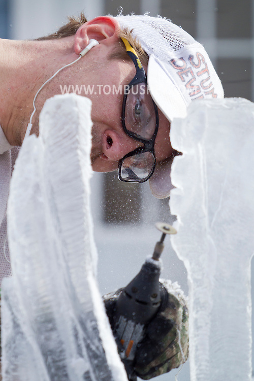 "Wurtsboro, New York - Ice carver Eric Polick works on his sculpture during a contest at the Winterfest on Feb. 8, 2014. Polick's sculpture ""Love, Peace & Music"" won second place. The festival is sponsored and organized by the Wurtsboro Board of Trade."