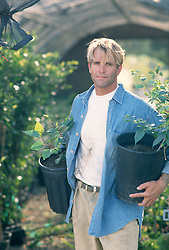 Good Looking Gardener holding two potted plants in a nursery