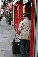 Man in doorway with suitcase Dublin Ireland