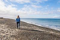 A woman hiking along Dungeness Spit, Washington State, USA.