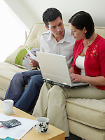 Couple using laptop sitting on sofa