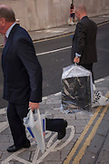 Two businessmen carry plastic bags across the street outside the Bank of England, in the City of London, England UK.