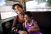 Rachna, 8, (right) a girl suffering from a severe neurological disorder, is riding the Chingari Trust Rehabilitation Centre's bus with her sister, Reena, 12, near the abandoned Union Carbide (now DOW Chemical) industrial complex in Bhopal, Madhya Pradesh, India, site of the infamous 1984 gas tragedy. The poisonous cloud that enveloped Bhopal left everlasting consequences that today continue to consume people's lives.