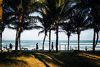 People walk along the beach promenade in the late afternoon sun in Danang, Vietnam.