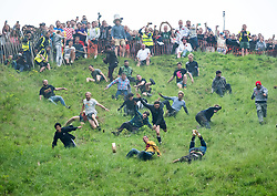 © Licensed to London News Pictures. 28/05/2018. Brockworth, Gloucestershire, UK. CHRIS ANDERSON (yellow top) on his way to winning the first race at the annual custom of Cheese Rolling at Coopers Hill. Participants chase a double Gloucester cheese down a very steep slope with the first to the bottom winning the cheese. The first men's race was won by king of the hill local Chris Anderson who is now the all time cheese rolling champion having won 21 Double Gloucester cheeses over the past 14 years. Photo credit: Simon Chapman/LNP