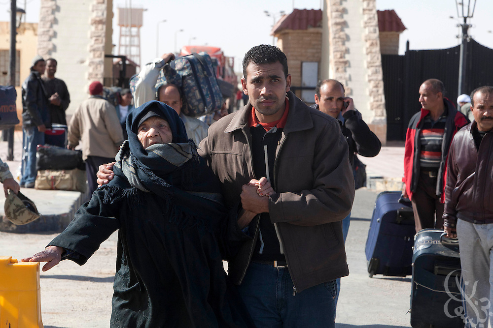An Egyptian man helps his ailing mother across the Egypt-Libya border at Saloum, Egypt with thousands of other Egyptians during ongoing protests and spreading revolution February 22, 2011 in neighboring Libya. .Slug: Libya.Credit: Scott Nelson for the New York Times