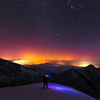 A mountaineer with head light looking at the sky full of stars