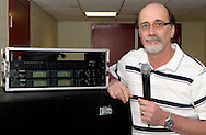 Victoria Theatre Association production manager Patrick Keough holds one of the Shure handheld wireless mics next to the antenna distribution system, where the receivers are, used at the Schuster Center in downtown Dayton, Friday, January 27, 2012.  Keough says this system works in the range of 638.350 to 643.075 Mhz instead of the higher bands they'd used before.  The higher the frequency, Keough  said, the better they work.