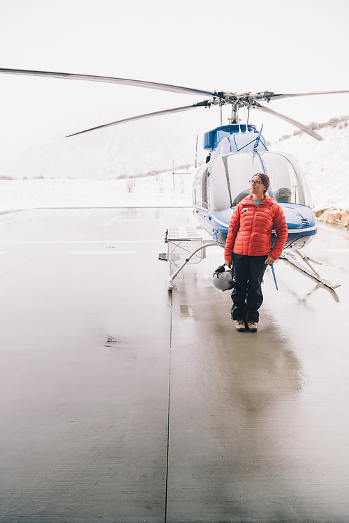 Nicole Ludwig standing in front of her Bell 407 Search And Rescue helicopter in Jackson Wyoming.