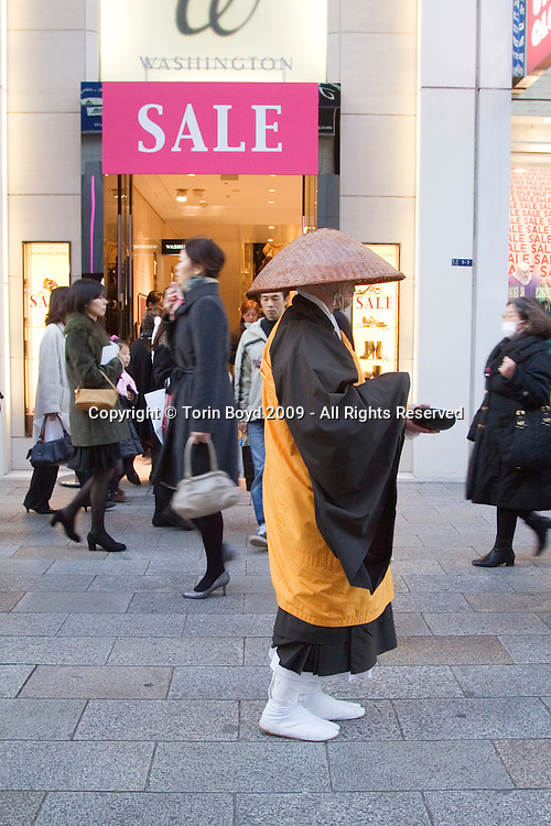 "This is a mendicant Buddhist monk in Tokyo's Ginza shopping district, which is the equivalent of New York's Fifth Ave. These type of ""beggar"" monks can occasionally be found in shopping districts and major train stations throughout Japanese metropolitan cities. Mendicant monks, priest and nuns of most major religions are those who rely exclusively on charity to survive. In Japan, this is an old custom that dates back centuries and does not reflect on the current Japanese recession. But this monk can be seen in front of a sale sign for the large Japanese shoe chain called Washington. Sales are quite prevalent in Japan in early 2009 even in the premier shopping Ginza shopping district."