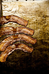 Four crispy slices of bacon being cooked on a grittle
