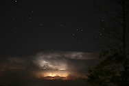Middletown, New York -  Lightning from distant thunderstorms lights up clouds on the horizon as star shine above in the night sky on July 17, 2010.