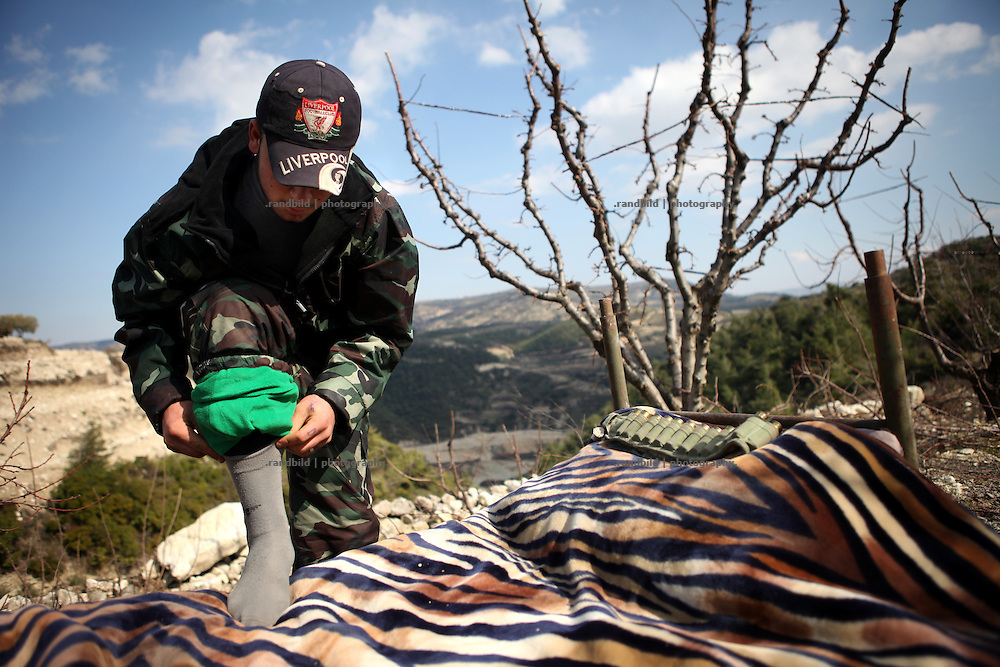 A Member of the Free Syrian Army dresses up in the morning in the mountains outside Al Janoudiyah, Province of Idlib, Syria.