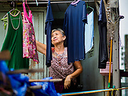 "22 MARCH 2018 - BANGKOK, THAILAND: One of the remaining residents alongside Khlong Lat Phrao hangs her laundry. Bangkok officials are evicting about 1,000 families who have set up homes along Khlong  Lat Phrao in Bangkok, the city says they are ""encroaching"" on the khlong. Although some of the families have been living along the khlong (Thai for ""canal"") for generations, they don't have title to the property, and the city considers them squatters. The city says the residents are being evicted so the city can build new embankments to control flooding. Most of the residents have agreed to leave, but negotiations over compensation are continuing for residents who can't afford to move.      PHOTO BY JACK KURTZ"