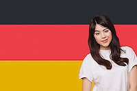 Portrait of smiling mixed race young woman against German flag