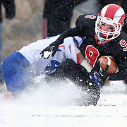 Cole Turpin, New Canaan, is tackled during the New Canaan Rams Vs Darien Blue Wave, CIAC Football Championship Class L Final at Boyle Stadium, Stamford. The New Canaan Rams won the match in snowy conditions 44-12. Stamford,  Connecticut, USA. 14th December 2013. Photo Tim Clayton
