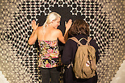 A woman and her friend admire the tactile feel of a quilted wall hanging from Mexico.