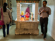 07 JANUARY 2014 - SINGAPORE:  People pray and circumnavigate the Navagraham at Sri Veeramakaliamman Temple, a Hindu temple located in Little India in the southern part of Singapore. The Sri Veeramakaliamman Temple is dedicated to the Hindu goddess Kali, fierce embodiment of Shakti and the god Shiva's wife, Parvati. Kali has always been popular in Bengal, the birthplace of the labourers who built this temple in 1881. Images of Kali within the temple show her wearing a garland of skulls and ripping out the insides of her victims, and Kali sharing more peaceful family moments with her sons Ganesha and Murugan. The building is constructed in the style of South Indian Tamil temples common in Tamil Nadu as opposed to the style of Northeastern Indian Kali temples in Bengal. PHOTO BY JACK KURTZ