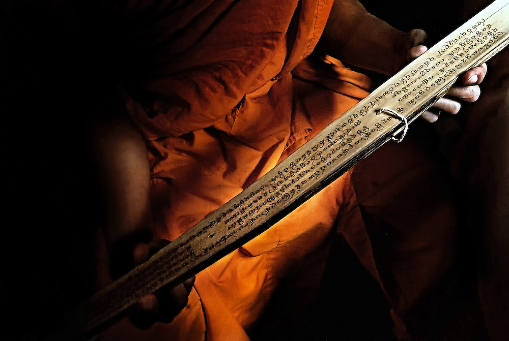 A Bhuddist novice reading religious text from a bamboo script in Luang Prabang, Laos.