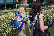 24 hours before the royal marriage of Prince William and Kate Middleton, two members of an NBC TV crew walk away after a live broadcast for Good Morning America outside Buckingham Palace. A picture of the royal couple appear on a bag carried by one of the women. Taking place on Friday 30th April in front of millions of Britons and foreign tourists (many American), the crowds are already gathering to claim their ideal locations in the front rows along the procession route.
