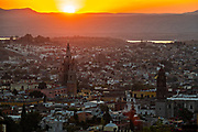 Colorful sunset over the Parroquia de San Miguel Arcangel and San Francisco church steeples in the historic city center viewed from the high point of Los Balcones in San Miguel de Allende, Mexico.