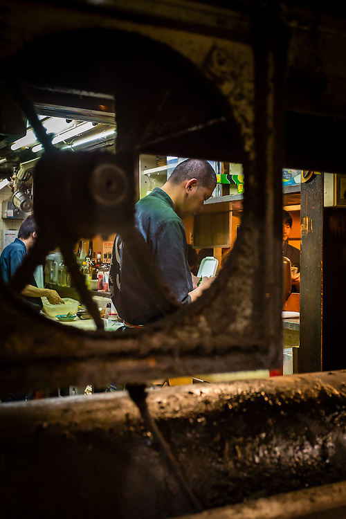 A cook from Omoide Yokocho seen through a fan.