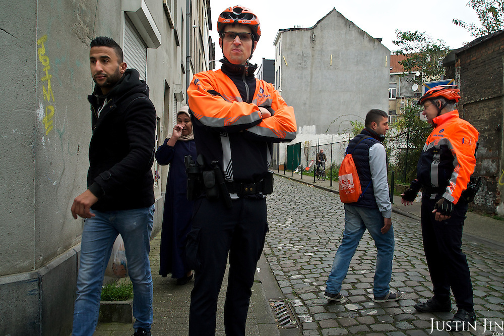 Police and passersby at Brussels' Molenbeek neighbourhood, a hotbed of Islamic fundamentalism.