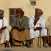 Oman, Ra's al-Hadd. February/07/2008...Men gathered together for a wedding in the fishing village of Ra's al-Hadd enjoy halwa, a traditional Omani treat, while discussing the day's events.
