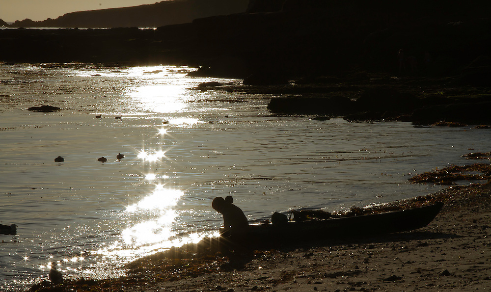 With brilliant sunspots glittering of the ocean a weary kayaker bundles his gear