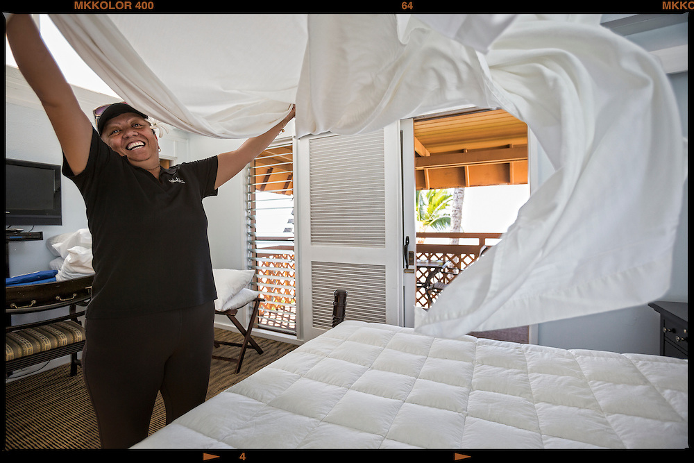 "Housekeeping Manager Lorraine Naomi Luuloa, 54,  puts the top sheet on bed at the Hotel Molokai where she has worked for almost 8 years.  ""Everyone here is like ohana and we all work very hard to make our jobs and life here easy living."