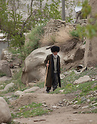 A Turkmen elder wearing a telpek sheeps' wool hat, walking in the village of Nohur