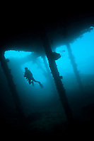 Diver exploring the hold of the USAT Liberty Glo wreck, Tulamben, Bali, Indonesia. Tulamben is located on Bali's NE coast and has become very popular with divers and photographers.  The area is famous for the wreck of the USAT Liberty Glo, a WWII era ship that lies just off the beach in Tulamben village.  The areas is also very well known for its high marine biodiversity. Bali is a very popular holiday destination for divers and offers a wide variety of different types of diving, from reefs and wrecks to mucks sites such as Puri Jati and Gilimanuk.
