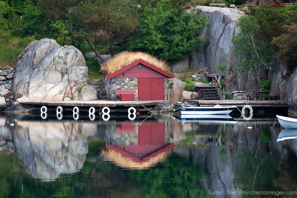 Europe, Norway, Stavanger. Boathouse, dock,  and reflection on Lysefjord.