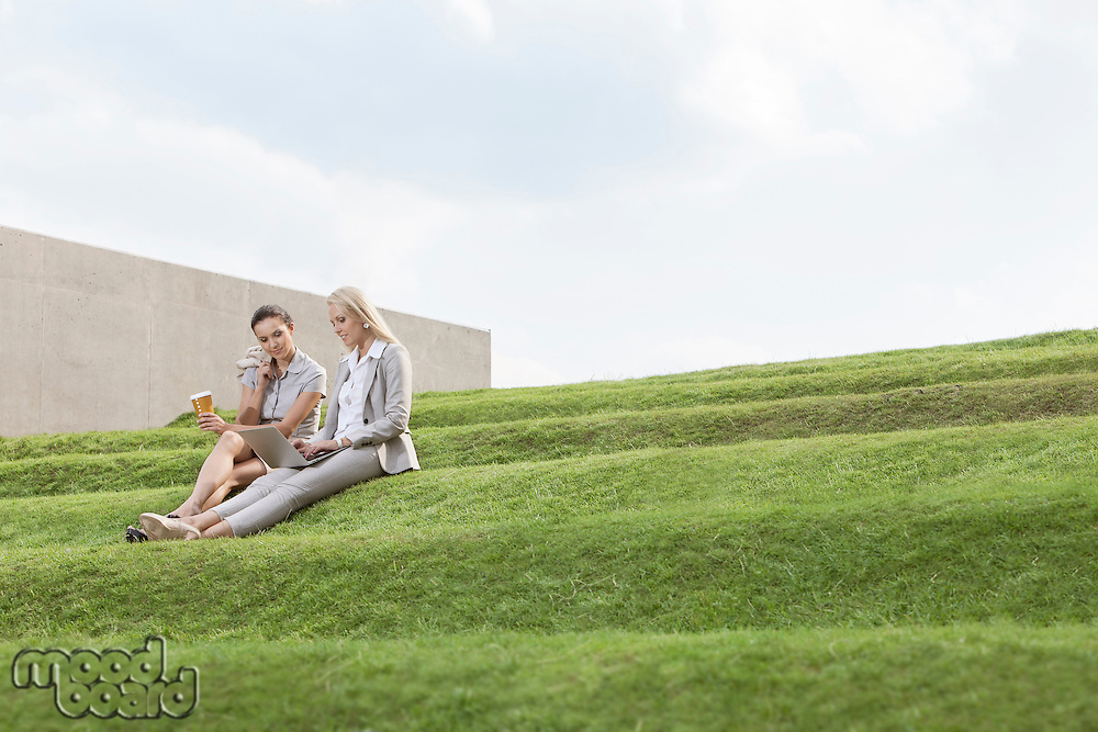 Full length of female business executives with disposable coffee cup and laptop sitting on grass steps against sky