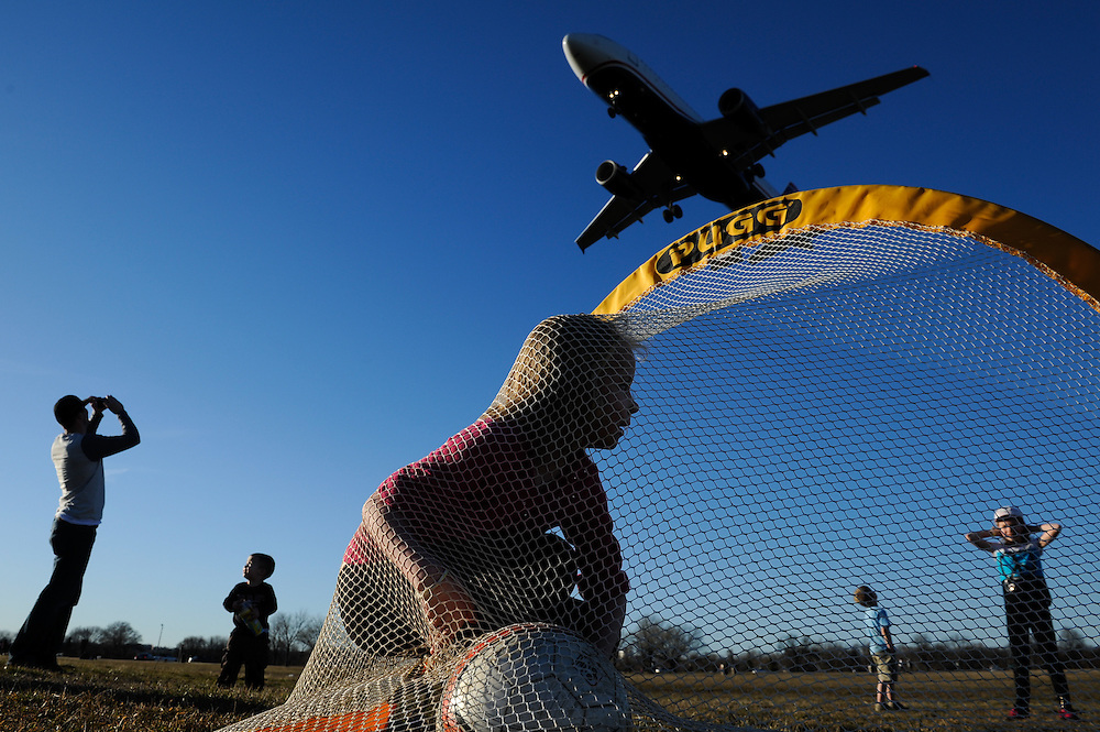 Leah Erb, 7, retrieves a soccer ball from a goal as a plane passes overhead at Gravelly Point Park in Arlington, VA.
