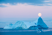 A full moon sets over an iceberg in the Gerlache Strait off the coast of the Antarctic peninsula.