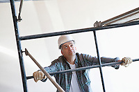 Construction worker standing near scaffolding while looking up