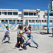 In Ein El-Hilweh refugee camp, home to 75.000 Palestinians. Boys play in the school yeard in the mroning heat. It is summer break in the UNWRA school and Naba'a runs Play and Learn sessions in the empty school for vulnerable children. They aim is to give them a safe space to express themselves with out fear of repression. Developmental Action Without Borders(Naba'a) work in Palestinian refugee camps across Lebanon to help children in the camps.  The camps are densely over-crowded and many of the children are 4th generation refugees living in Lebanon with no citizenship or rights and under immense pressure. Naba'a is a mix of Palestinians and Lebanese and aim to give children a sense of security and freedom to express their needs and rights.Naba'a operates in communities governed by a multitude of political parties and religious groups and Naba'a keeps a strict independed line from any affiliation with any groups.