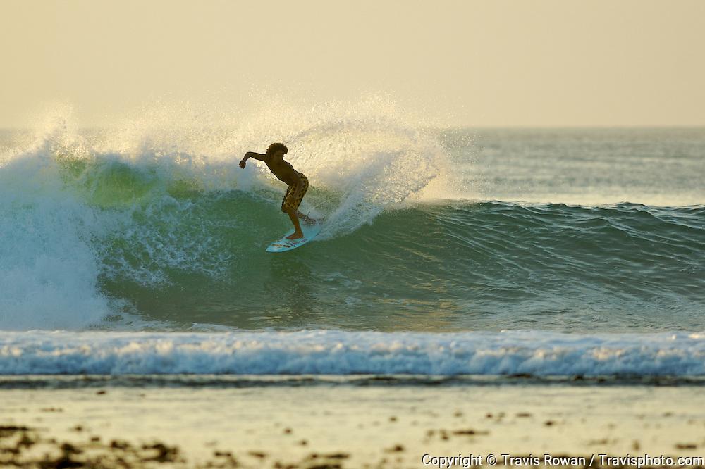 Hawaiian surfer, Kealii Mamala, has a relaxing surf at Bingin beach in Bali.