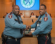 Houston ISD officer Quinten Flannel, left, is recognized as district employee of the month by assistant chief Michael Benford, right, during the Houston ISD Board of Education meeting, March 13, 2014.