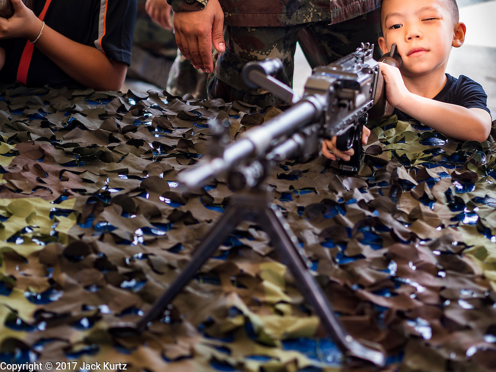 """14 JANUARY 2017 - BANGKOK, THAILAND: A Thai child looks down the sightes of a FN MAG machine gun during Children's Day activities at the King's Guard, 2nd Cavalry Division base in Bangkok. Thailand National Children's Day is celebrated on the second Saturday in January. Known as """"Wan Dek"""" in Thailand, Children's Day is celebrated to give children the opportunity to have fun and to create awareness about their significant role towards the development of the country. Many government offices open to tours and military bases hold special children's day events. It was established as a holiday in 1955.       PHOTO BY JACK KURTZ"""
