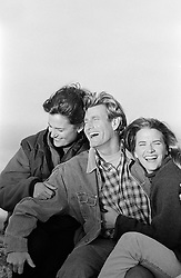 Three friends laughing and holding one another
